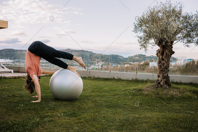 Flexible male in activewear leaning on fit balls and doing yoga in Camatkarasana on green lawn during pilates training