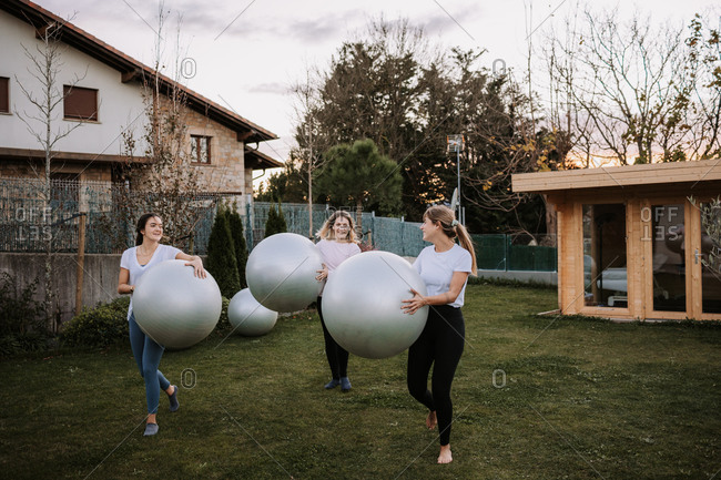 Group of cheerful slim females walking on lawn with fit balls after active pilates workout and looking at each other