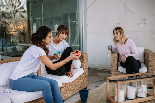 Smiling female friends sitting on cozy terrace near house and watching video together on smartphone