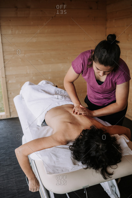 From above of crop unrecognizable female therapist applying lotion and preparing for doing massage for client in spa salon