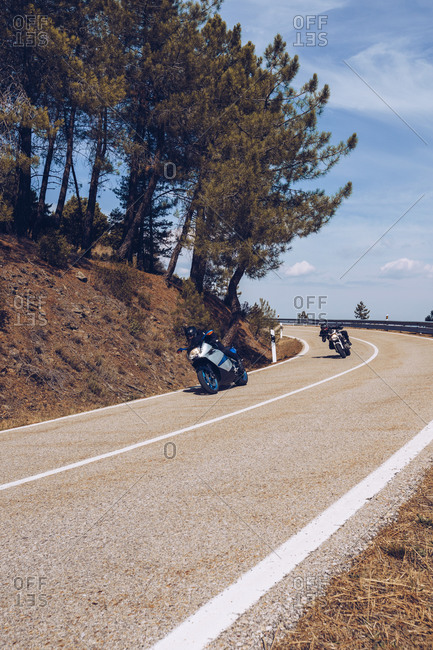 Motorcyclists in helmets riding modern motorbikes along curved asphalt roadway on sunny day