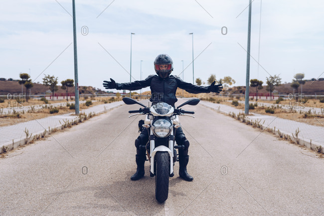 Full body of unrecognizable motorcyclist in black outfit and helmet sitting on modern motorbike parked on roadway