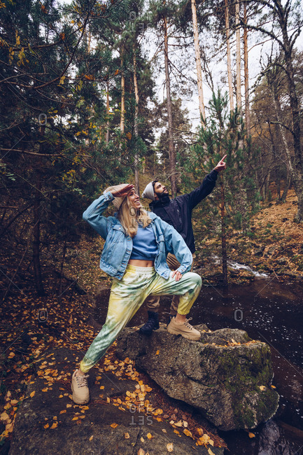 Side view of traveling couple standing in forest in fall and looking up while enjoying nature