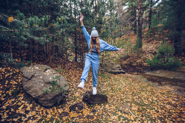 Delighted female tourist in warm casual tracksuit standing with outstretched arms on rock in autumn woods during vacation