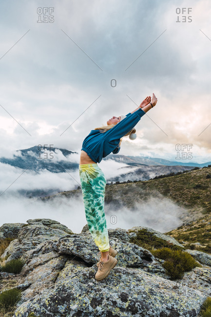 Side view of female explorer standing on rock with raised arms and enjoying nature and freedom during vacation in highlands