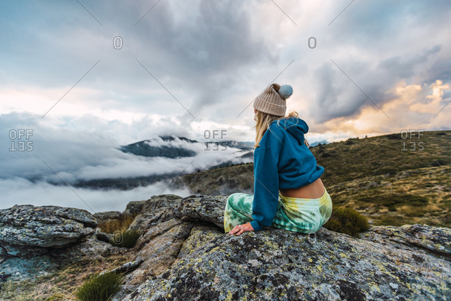 Side view of female explorer sitting on rock enjoying nature and freedom during vacation in highlands