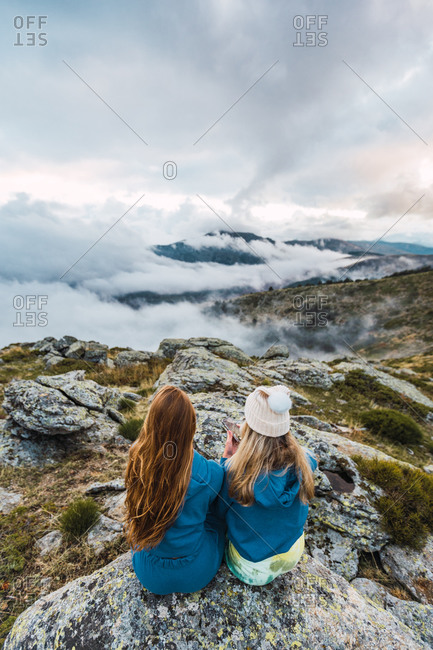 Back view of unrecognizable delighted female friends sitting on rock together while enjoying summer adventure in highlands