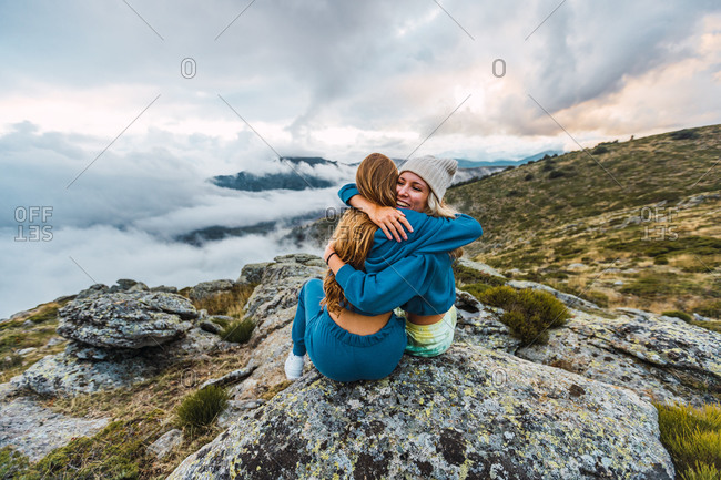 Delighted female friends sitting on rock and embracing while enjoying summer adventure in highlands