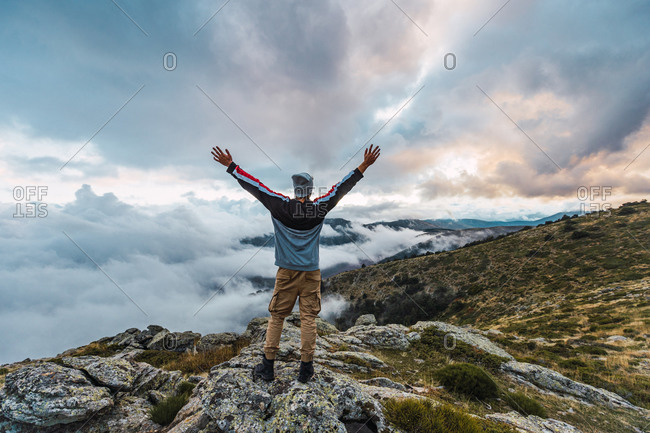 Back view of male hiker standing with outstretched arms on top of hill and enjoying freedom in highlands during adventure