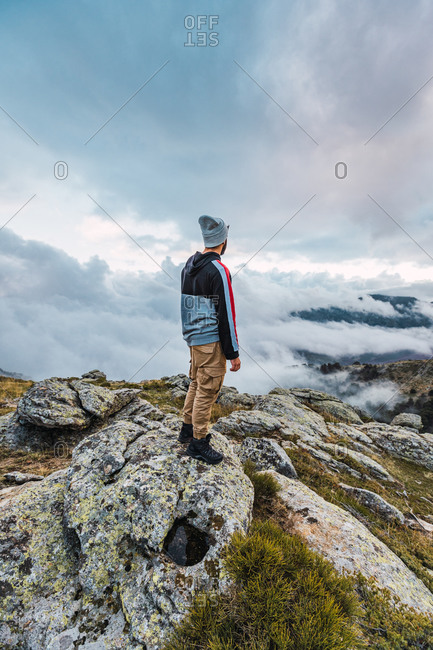Back view of male hiker standing on top of hill and enjoying freedom in highlands during adventure