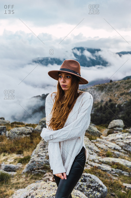 Thoughtful female traveler in hat standing on rocks in mountains while enjoying freedom and nature looking away