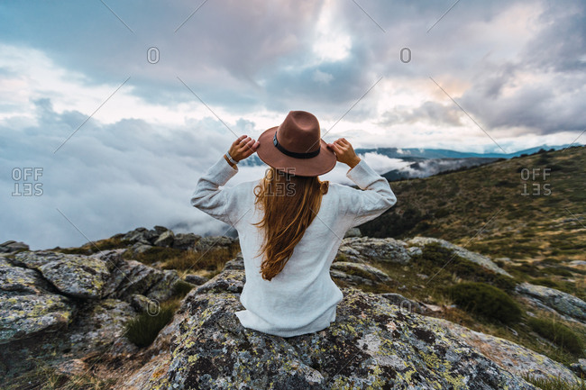 Back view of faceless female tourist in hat sitting on stone and observing scenic view of mountains on cloudy day