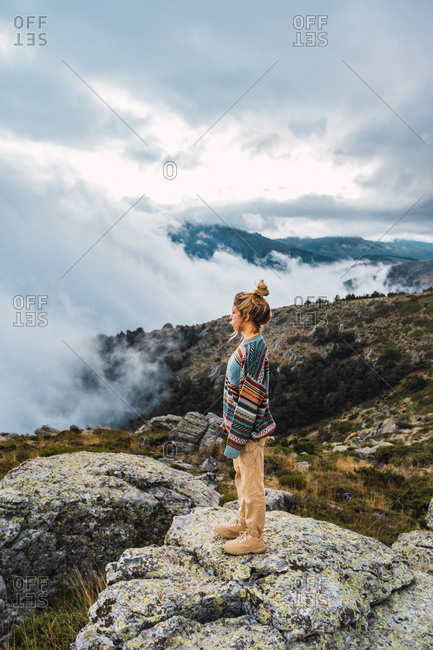 Side view of female explorer standing on rock enjoying nature and freedom during vacation in highlands