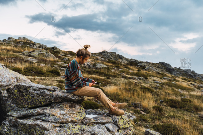 Side view of female tourist sitting on rough rock and using smartphone while relaxing during trekking in mountains