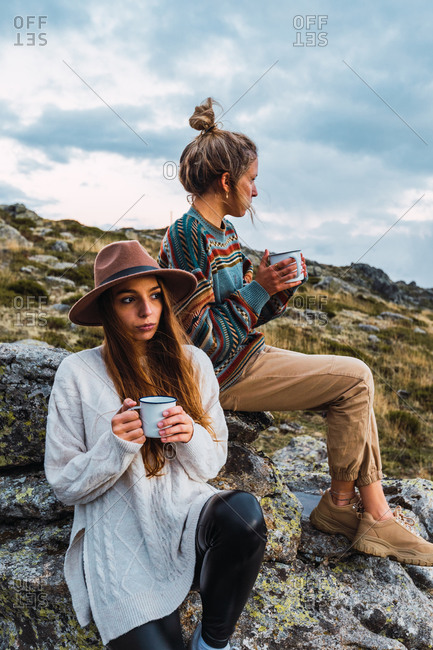 Peaceful female travelers resting with mugs of hot drinks on rocks in mountains and admiring picturesque landscape during adventure