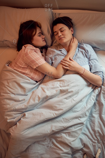 From above couple of lesbians in love resting sleeping on soft bed with eyes closed enjoying morning in bedroom