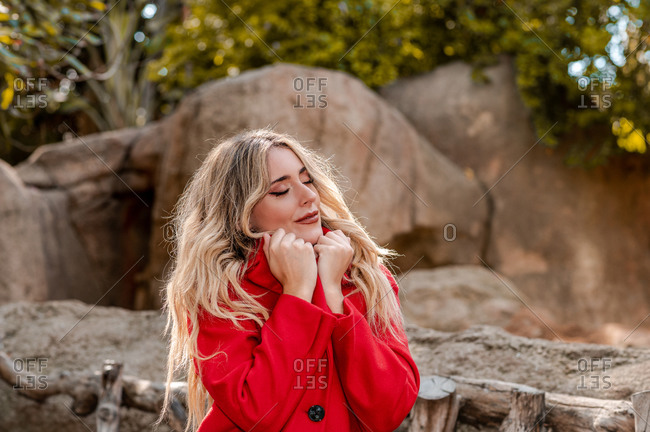 Tranquil female in red coat standing with closed eyes in park and enjoying nature in autumn