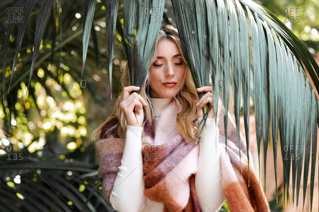 Charming gentle female wrapped in warm plaid stranding near palm tree and touching leaves while closed eyes
