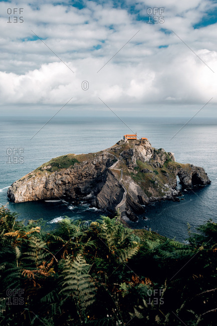 Breathtaking view of rocky Gaztelugatxe island in calm sea water under sky with clouds in Spain