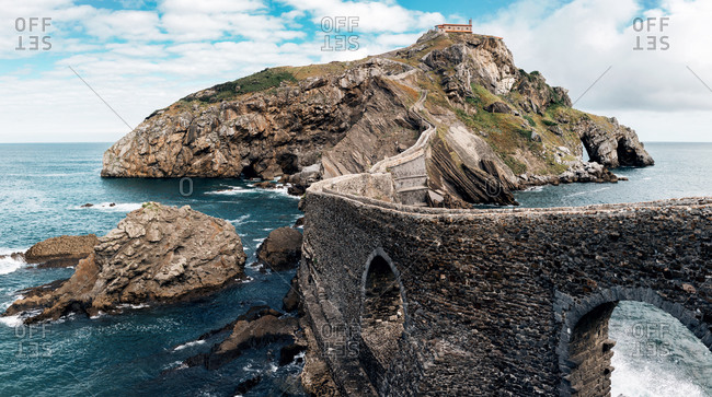 Spectacular panoramic scenery of rocky island of Gaztelugatxe and long stone bridge located in sea in Spain
