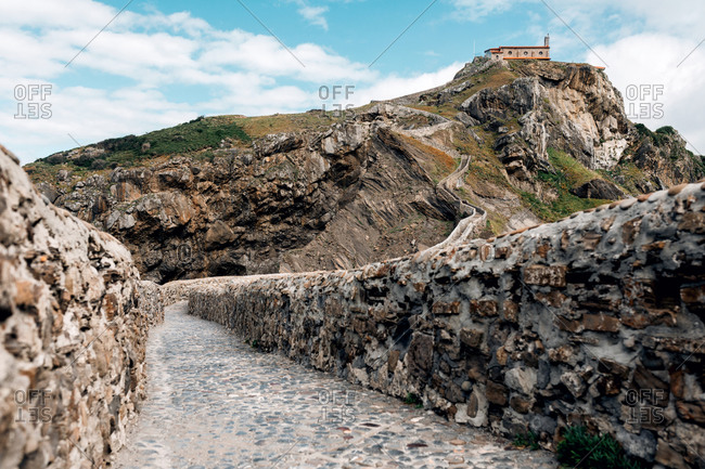 Empty road leading along stone bridge and ridge of rocky hill to lonely country house on island Gaztelugatxe surrounded by tranquil sea water with white foam waves during sunset