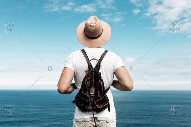 Back view of male tourist with backpack admiring scenic view of sea during summer holiday on Gaztelugatxe island