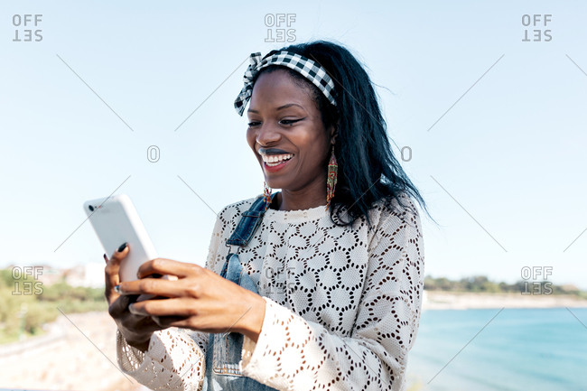 Cheerful young African American female in stylish outfit browsing mobile phone while standing on sandy seashore in sunny summer day
