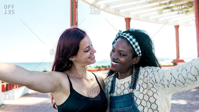Joyful multiracial lesbian girlfriends cuddling and taking selfie on mobile phone while enjoying summer day together at seaside