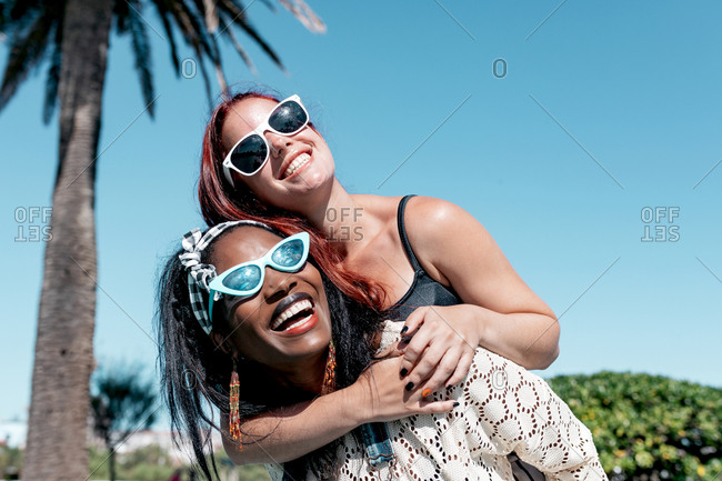 Delighted young multiethnic girlfriends in stylish sunglasses laughing brightly while having fun together in sunny summer day in tropical park