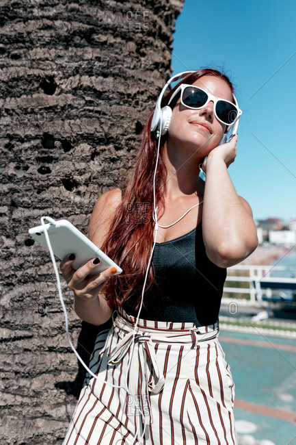 Trendy young female in stylish summer outfit and sunglasses enjoying music through headphones and smartphone while chilling on street in sunny day