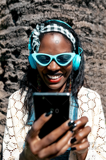 Cheerful young African American female in stylish summer outfit and sunglasses enjoying music through headphones and smartphone while chilling on street in sunny day