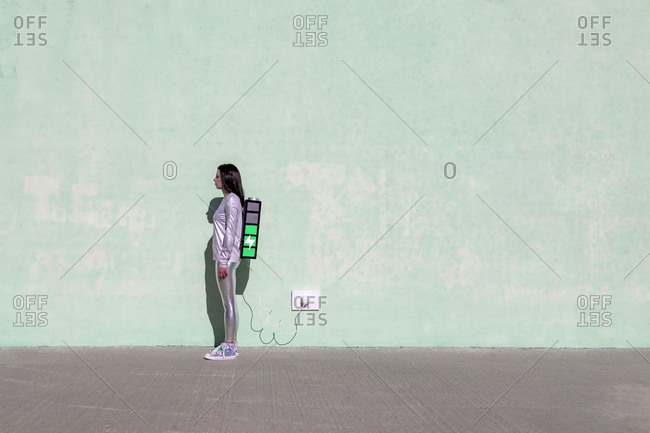 Side view of young fit female in trendy outfit standing on street with creative backpack connected to charger and having phone conversation