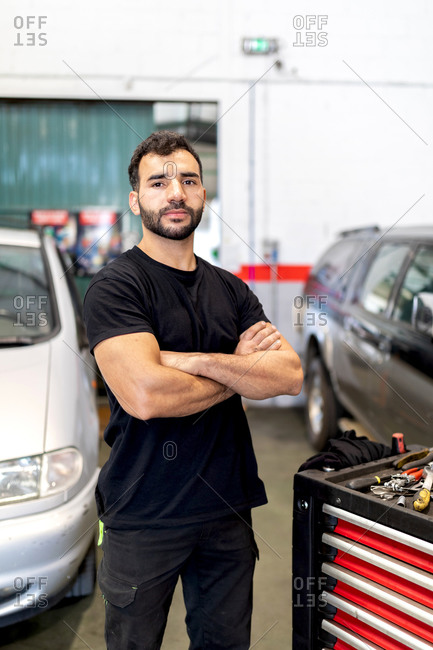 Serious male technician in gloves walking with tool cabinet in modern car service