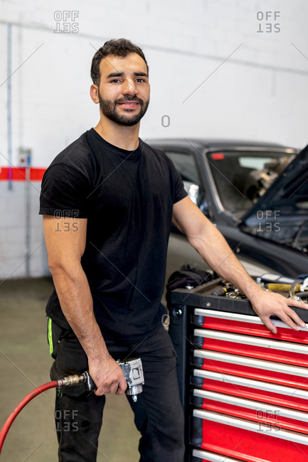 Male technician in gloves walking with tool cabinet in modern car service