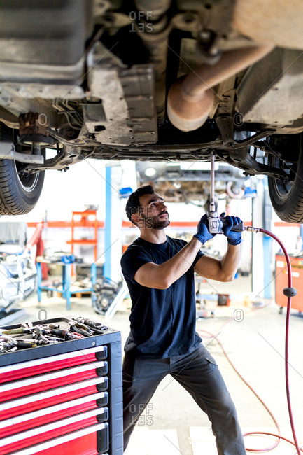 Busy male technician using special instrument and fixing car while working in modern service