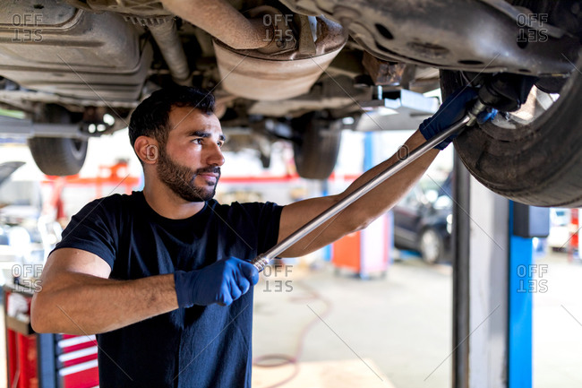 Focused male mechanic with metal wrench screwing detail of car wheel while working in service