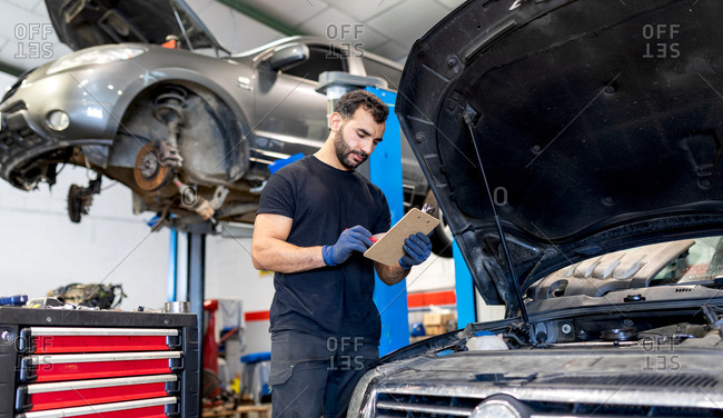male technician analyzing chart on clipboard while working in modern automobile workshop and examining car