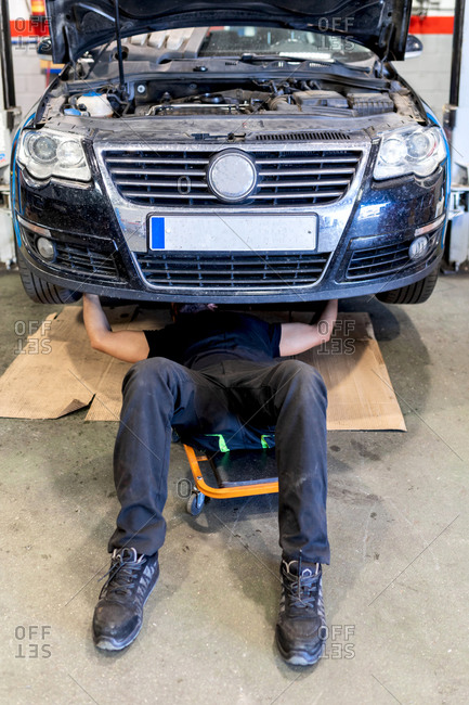 High angle of crop anonymous male mechanic lying on car creeper and examining details of automobile while working in modern service