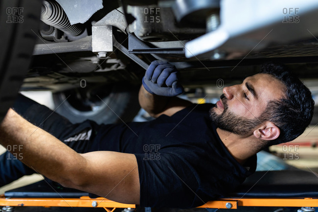 Side view of male technician lying on car creeper and screwing part of automobile wheel with metal spanner in modern service