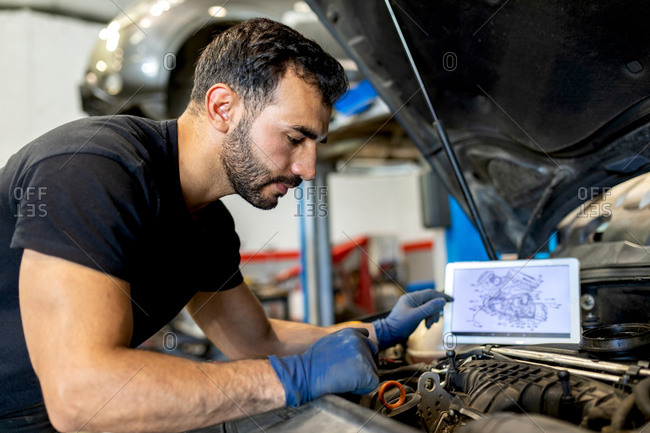 Side view of male technician with scheme of motor on tablet checking car engine during diagnostics in modern service