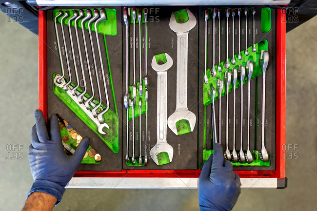 Top view of crop unrecognizable male technician standing near tool cabinet with collection of various spanners in car service
