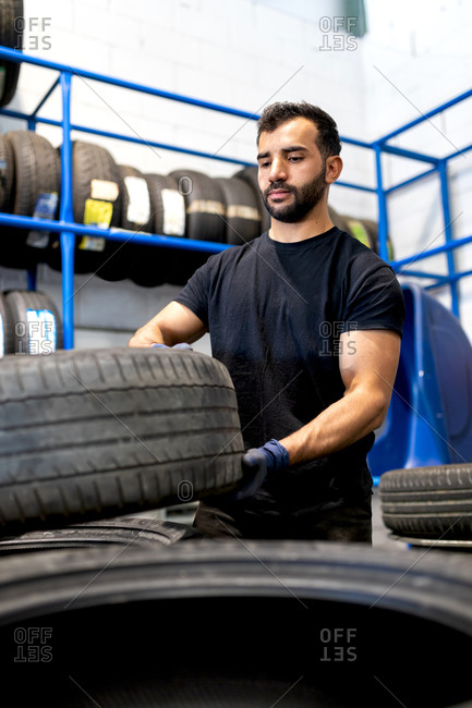 Serious bearded male mechanic standing with various car tires while working in service