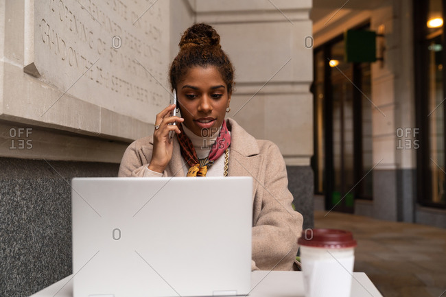 Stylish young African American female freelancer in trendy outfit talking on mobile phone and working remotely on laptop in cafe