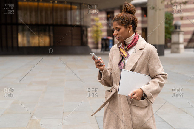 Side view of young African American female entrepreneur with curly hair in elegant coat using smartphone while crossing road in London with laptop in hand