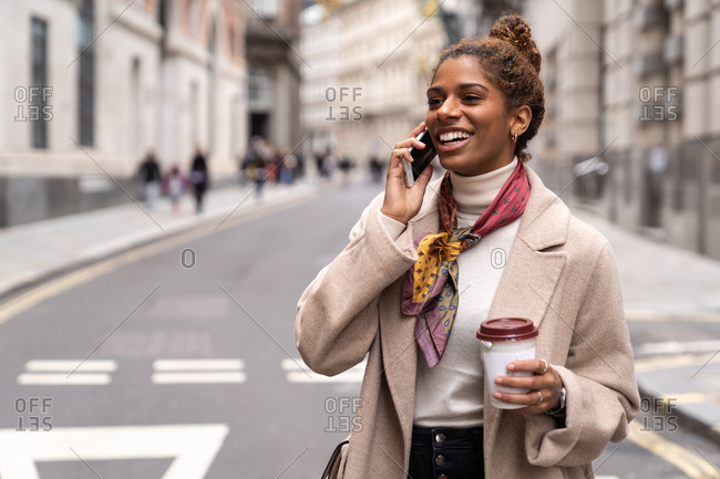 Side view of young ethnic lady in stylish coat walking on city square and having phone conversation in London