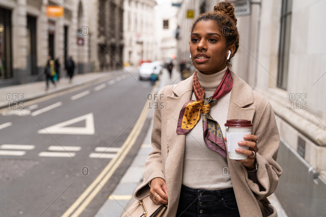 Confident young African American female entrepreneur in fashionable outfit listening to music with wireless earphones and drinking takeaway coffee while walking on city street during break