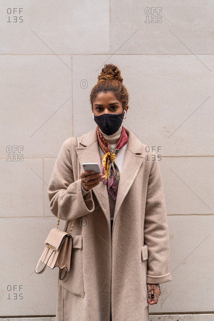 Trendy young ethnic woman in elegant coat and face mask with bag standing near wall and talking on smartphone using wireless earphones