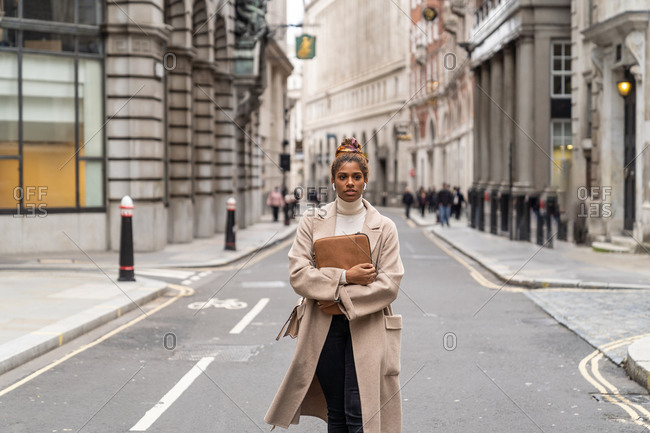 Thoughtful young African American female in trendy coat listening to music in true wireless earbuds while walking on London street with laptop in hand