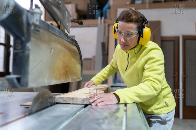 Side view of focused adult female artisan in goggles and headphones sawing wooden board with sharp circular saw in workshop