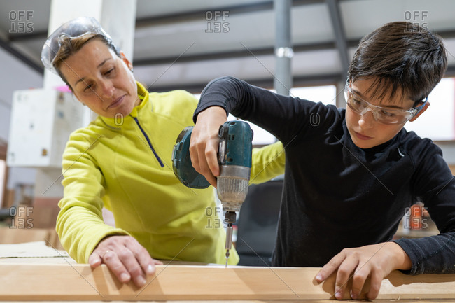 Concentrated boy in protective goggles using drill while helping middle aged mother during carpentry works